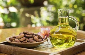jug of almond oil next to bowl of almonds