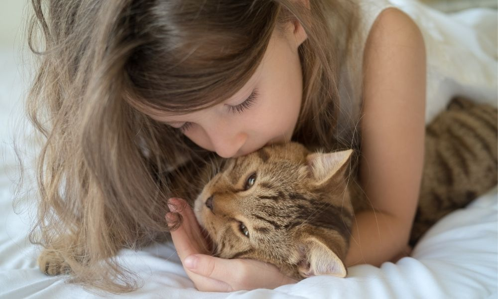 a young girl hugging her cat